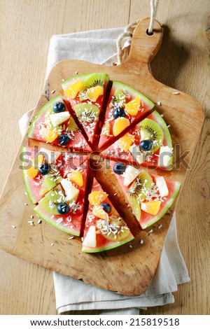 Overhead view of a colorful tropical fruit watermelon pizza topped with kiwifruit, blueberries, orange, pineapple, and sprinkled with desiccated coconut cut into segments on a rustic wooden board - stock photo