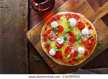 Overhead view of a colourful gourmet Italian pizza with a variety of cheeses, tomato and fresh basil on a wooden chopping board on an old rustic wooden table with copyspace - stock photo
