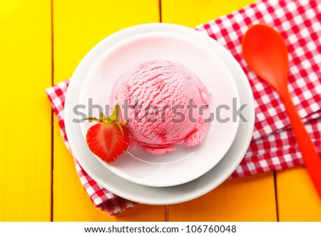 Overhead view of a country meal of strawberry icecream served on a colourful red and white checkered napkin on a yellow wooden tabletop - stock photo