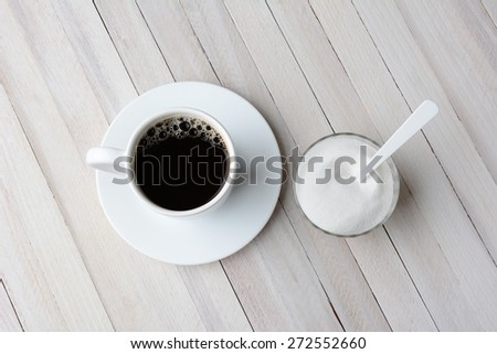 Overhead view of a cup of coffee and a bowl of granulated sugar with a plastic white spoon. Horizontal format on a rustic whitewashed table. - stock photo