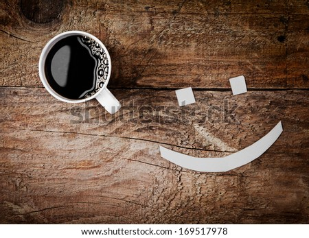 Overhead view of a cup of hot strong black espresso coffee with a smiling face with sugar cube eyes on a rough textured wooden background - stock photo