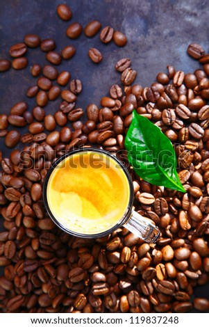 Overhead view of a cup of rich frothy coffee standing in scattered whole roasted coffee beans with a green leaf for decoration - stock photo