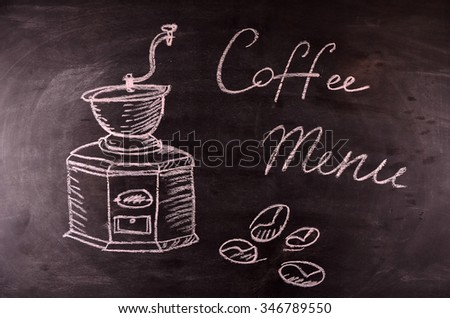 Overhead view of a fresh cup of coffee and a flaky croissant on an old school slate over a rustic wooden background,With text menu on blackboard - stock photo