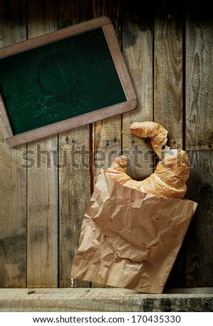 Overhead view of a freshly baked golden croissant, a cup of full roast espresso coffee and an old blank school slate for a menu or text on rustic wooden boards - stock photo