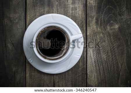 Overhead view of a freshly brewed mug of  black  coffee on rustic wooden background