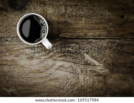 Overhead view of a freshly brewed mug of espresso coffee on rustic wooden background with woodgrain texture and cracks, with copyspace - stock photo