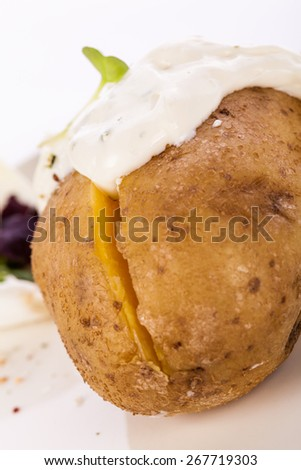 Overhead view of a healthy oven baked jacket potato with sour cream sauce garnished with endive leaves and fresh herbs