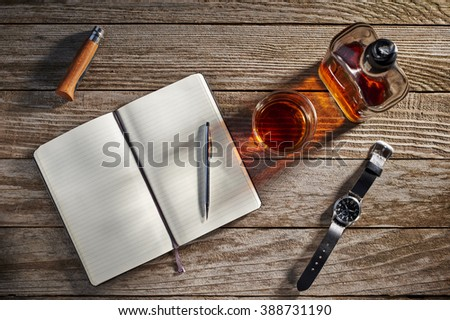 overhead view of a journal, pen, watch, knife, and whiskey - stock photo