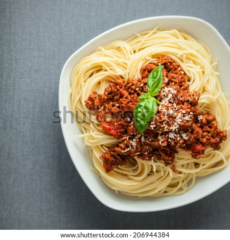 Overhead view of a large bowl of traditional Italian spaghetti pasta with a rich tomato and ground beef Bolognese topping garnished with fresh basil and parmesan cheese - stock photo
