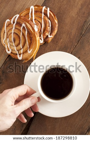 Overhead view of a mans hand reaching out to take a cup of rich espresso coffee and fresh Danish pastries for breakfast - stock photo