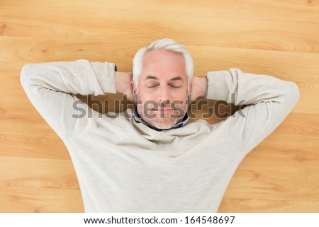Overhead view of a mature man sleeping on parquet floor at home