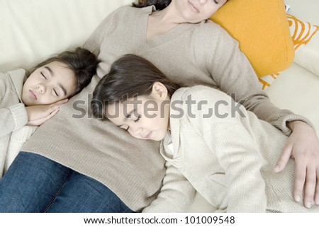 Overhead view of a mother and two twin daughters sleeping on a sofa. - stock photo