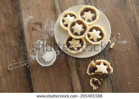 Overhead view of a plate of decorative freshly baked Christmas mince pies with pastry stars alongside a half eaten pie and strainer with icing sugar to dust the top - stock photo