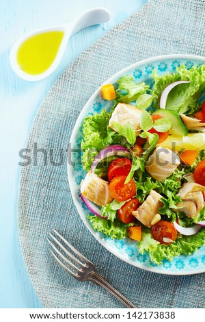 Overhead view of a plate of delicious cold seafood salad with pieces of salmon fillet on a bed of lettuce, tomato and onion served with sliced lemon - stock photo