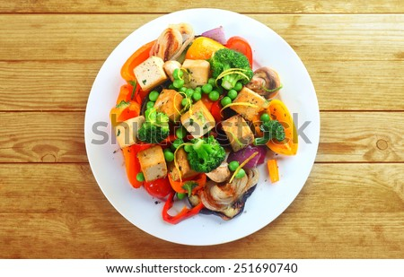 Overhead view of a plate of healthy grilled roast vegetables with tofu, or soybean curd, on a wooden table - stock photo