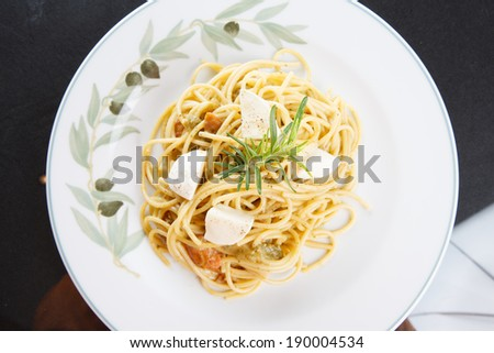 Overhead view of a plate of savory Italian spaghetti with mozzarella cheese garnished with a sprig of fresh rosemary served on a dark surface - stock photo