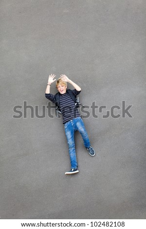 overhead view of a playful teen boy lying on ground - stock photo