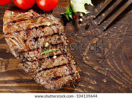 Overhead view of a portion of juicy grilled beef steak with peppercorns on a textured wooden surface - stock photo