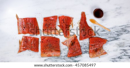 Overhead view of a raw red salmon fillets with seasonings and maple syrup on natural marble stone counter. Preparing fish for smoke cooking.