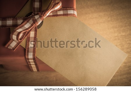 Overhead view of a red Christmas gift box, tied with gingham ribbon on a wooden table.  Old parcel tag faces upwards with empty space for message.  Low saturation for  vintage or retro appearance. - stock photo