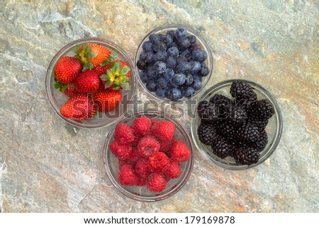 Overhead view of a selection of different fresh berries in glass jars including succulent ripe strawberries, blackberries, blueberries and raspberries for a healthy snack or dessert on a stone counter - stock photo