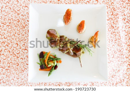 Overhead view of a serving of roast lamb cutlets seasoned with rosemary and gravy and served with fresh roast vegetables - stock photo