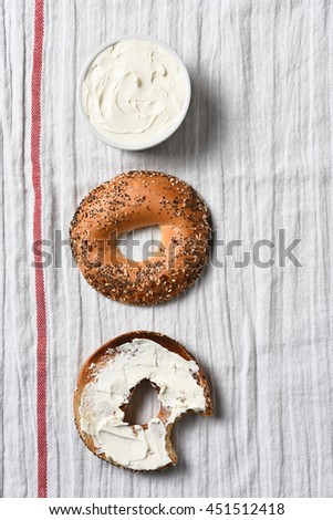 Overhead view of a sliced bagel, one half spread with cream cheese. A crock full of spread on a kitchen towel. - stock photo