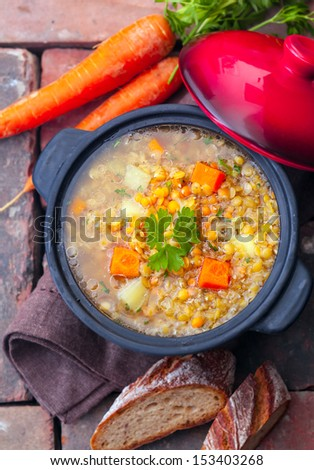 Overhead view of a thick wholesome vegetarian vegetable and lentil stew served with sliced bread on bricks - stock photo