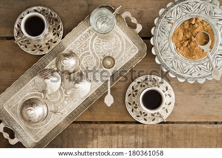 Overhead view of a tray set with cezve for heating the pulverised or ground coffee beans and two cups of freshly brewed traditional Turkish coffee served with brown sugar - stock photo