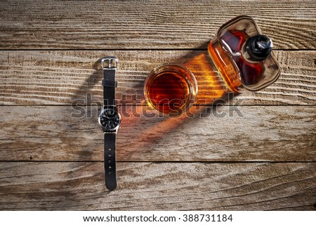 overhead view of a watch and whiskey - stock photo