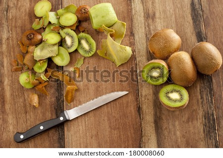 Overhead view of a wooden kitchen counter with a knife and fresh kiwi fruit that are being peeled and diced for a healthy delicious tropical dessert - stock photo