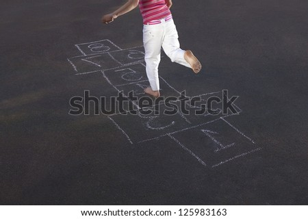 Overhead view of a young girl skipping through a game of hopscotch marked out on an asphalt surface