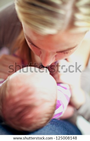 Overhead view of a young mother and her tiny newborn baby bonding with their noses close together sharing an intimate tender moment - stock photo