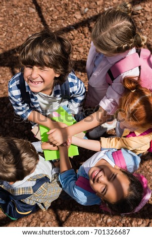 overhead view of adorable multiethnic kids stacking hands above books and smiling at camera