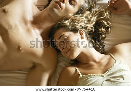 Overhead view of an attractive young couple laying down in bed, sleeping in a warm light. - stock photo