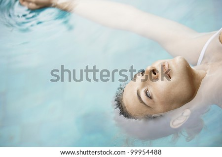 Overhead view of an attractive young woman floating on blue water. - stock photo