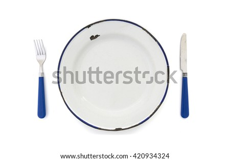 Overhead View of an old enamel plate with blue knife and fork on a white background