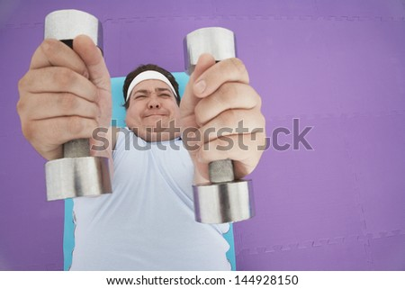 Overhead view of an overweight man lying down and lifting dumbbells  - stock photo