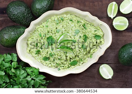 Overhead view of Avocado Lime Cilantro Rice with fresh ingredients against a rustic wooden background. - stock photo