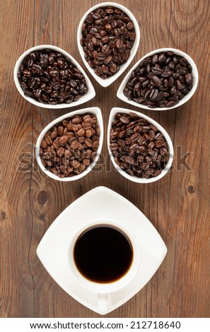 Overhead view of black coffee with several varieties of fresh roasted coffee beans on a brown wooden background - stock photo