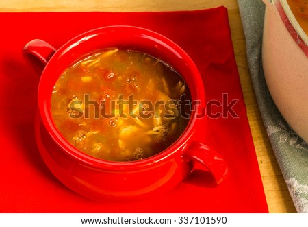 Overhead view of bowl of chicken taco soup on red napkin fresh from large pot. - stock photo