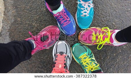Overhead view of 6 brighlty colored runners' shoes on wet pavement - stock photo