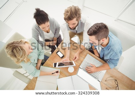 Overhead view of business people with digital tablet while sitting at desk in office - stock photo