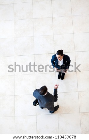 overhead view of businessman talking to businesswoman - stock photo