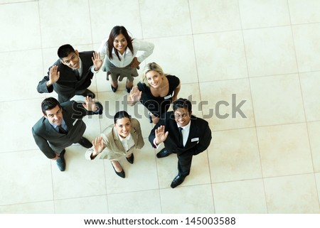 overhead view of businesspeople looking up and waving - stock photo