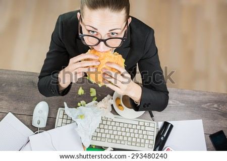 Overhead View Of Businesswoman eating At Computer In Office at work place. The modern pace of life there is no time for healthy eating - stock photo