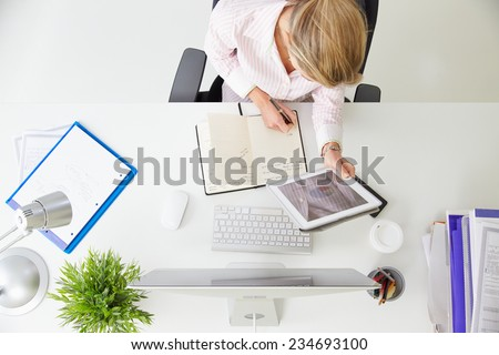 Overhead View Of Businesswoman Working At Computer In Office - stock photo