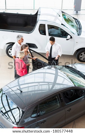 overhead view of car dealer showing new car to customers - stock photo
