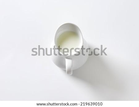 overhead view of ceramic jug with freshly milked milk - stock photo