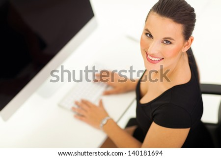 overhead view of cheerful businesswoman working on a modern computer - stock photo